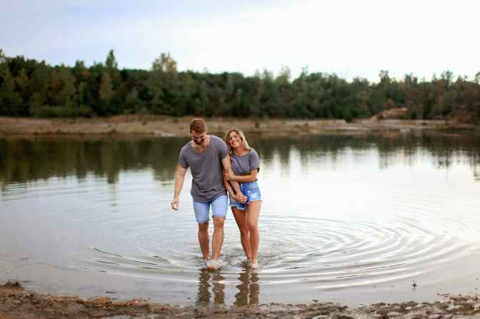 couple wearing grey t shirts walking on shallow water and smiling